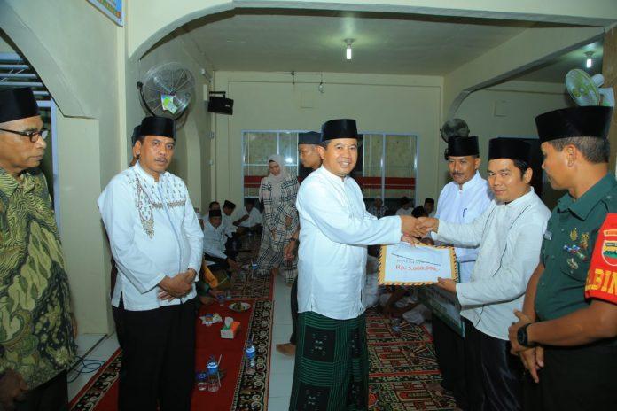 Sekda Rohul, H Abdul Haris menyerahkan santunan kepada salah seorang tokoh masyarakat