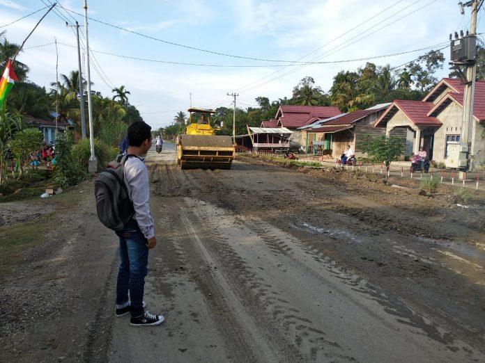 Aktivis Muda Rokan Hulu, Alfa Syahputra tengah melihat Dinas PUPR Rohul memperbaiki jalan rusak tersebut