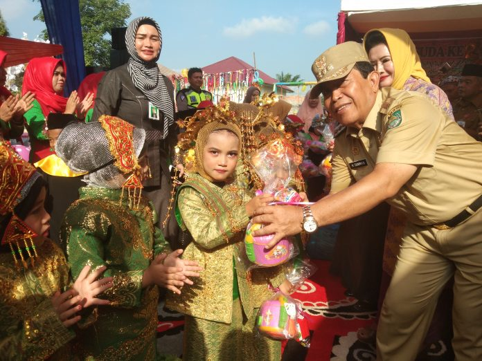 Bupati Rohul, H Sukiman didampingi Hj Peni Herewati Sukiman memberikan cenderamata kepada siswa TK Yayasan Azza