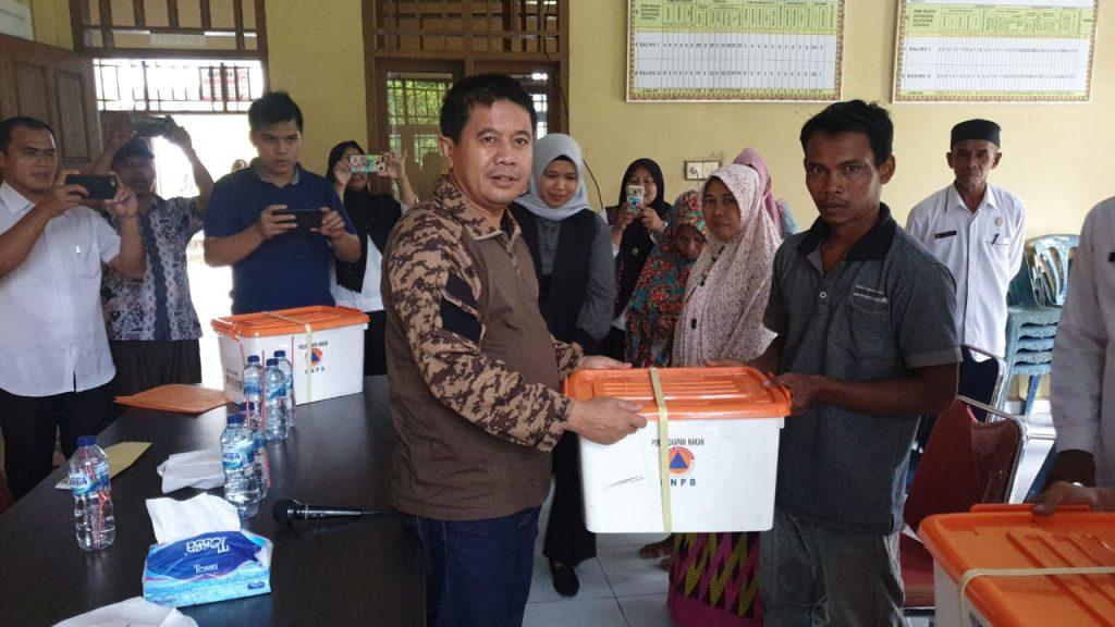 Sekda Rohul memberikan bantuan secara simbolis, berupa kebutuhan sehari-hari kepada perwakilan warga yang rumahnya terkena puting beliung