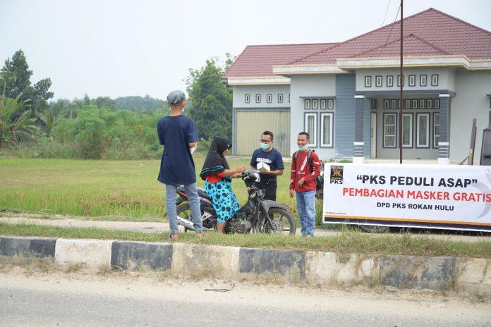 anggota DPRD Rokan Hulu, dari fraksi PKS, H Depredi Kurniawan saat membagi masker kepada masyarakat