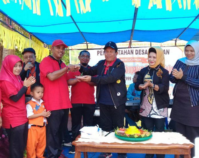 Usai memotong tumpeng, Bupati Rohul, H Sukiman memberikan sebagian nasi tumpeng kepada Kades Alahan, Heri Susanto