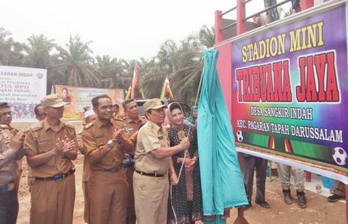 Bupati Rohul, H Sukiman didampingi Ketua TP PKK Rohul, Hj Peni Herawati Sukiman tengah meresmikan Stadion mini Tribuana Jaya