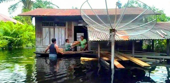Babinsa Koramil 10 Kunto Darussalam Kodim 0313/KPR Peltu M Sitepu menyerahkan bantuan kepada warga korban banjir