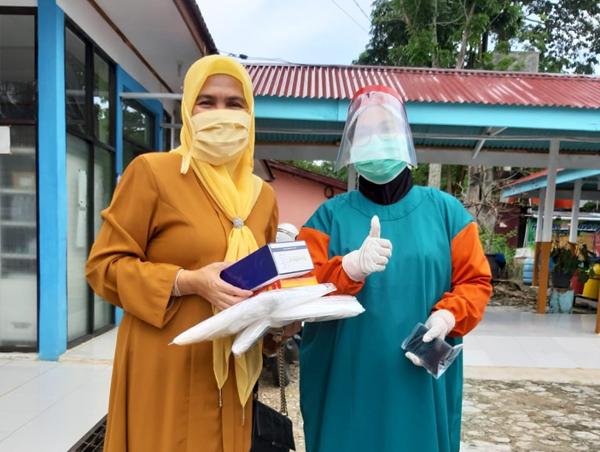 Anggota DPRD Rokan Hulu Fraksi Golkar, Hj Hasmeri Yulinawati menyerahkan APD kepada salah satu tenaga medis di Puskesmas Rambah