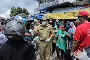 Bupati Rohul H Sukiman memberikan masker gratis yang disalurkan PMI Rohul kepada pengunjung Pasar di Kecamatan Ujung Batu