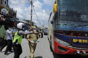 Bupati Rohul H Sukiman bersama Unit Lantas Polsek Ujung Batu memberhentikan salah satu Bus AKAP saat melintasi ruas jalan Ujung Batu, memberikan masker gratis dari PMI Rohul