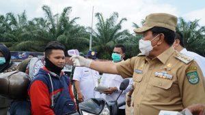 Bupati Rohul H Sukiman langsung melakukan thermo screning kepada salah seorang pengendara sepeda motor, saat meninjau kondisi Posko Covid-19 yang didirikan di daerah perbatasan pintu masuk kabupaten Rohul