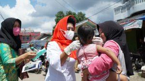 Ketua PMI Kabupaten Rohul Hj Peni herawati Sukiman sedang memasangkan masker keapda salah seorang balita saat pemberian masker kepada pengunjung pasar desa di Kecamatan Rambah Samo